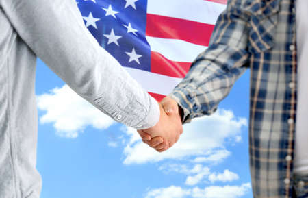 Men shaking hands and American flag on sky background. Support concept