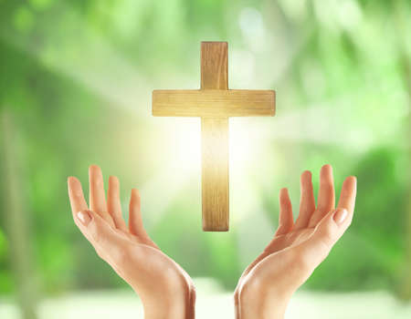 Freedom of religion concept. Female hands with wooden cross on blurred background
