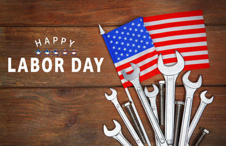 Text HAPPY LABOR DAY with American flag and tools on wooden background