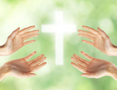Freedom of religion concept. Female hands with cross on blurred background