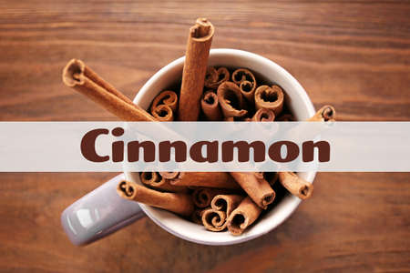 Cup with cinnamon sticks on wooden background