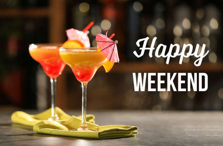 Glass of delicious cocktail on table. Text HAPPY WEEKEND on background