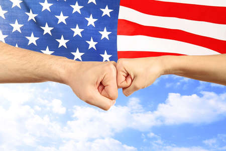 Hands and American flag on sky background. Patriotic concept Stock Photo