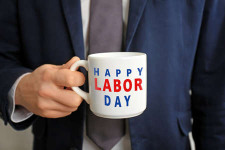 Man holding cup with text HAPPY LABOUR DAY, closeup