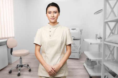 Giovane estetista asiatica nel salone della stazione termale al lavoro