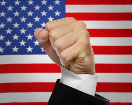 Male fist and American flag on background. Patriotic concept Stock Photo