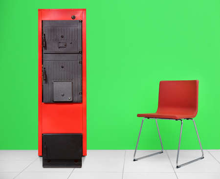 Energy savings concept. Solid fuel boiler and chair on color wall background Stock Photo