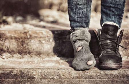 貧困の概念。タッターソックスとブーツ1本を着ている貧しい女性