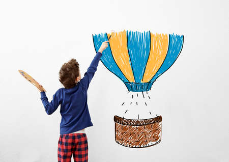 Childhood concept. Little painter drawing balloon on white wall background