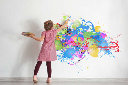Childhood concept. Little painter drawing abstract picture on white wall background