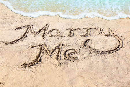Text MARRY ME written on sand near water. Romantic concept
