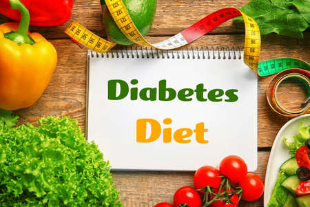 Notebook with text DIABETES DIET and healthy food on wooden background. Health care concept