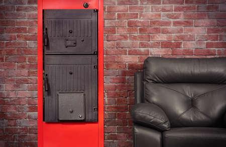 Energiebesparend concept. Vaste brandstofketel en fauteuil tegen bakstenen muurachtergrond% 00