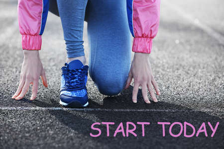 Woman on start line of race track at stadium. Fitness quotes