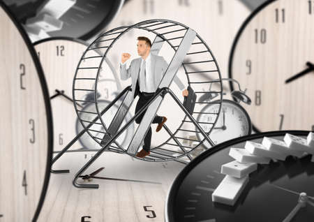 Young man running in wheel and clocks on background. Business rat race concept