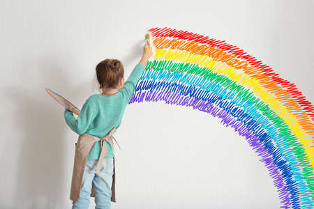 Childhood concept. Little painter drawing rainbow on white wall background