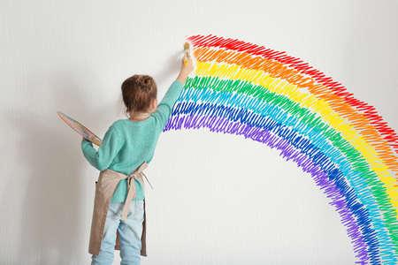 Kindheitskonzept . Kleiner Maler zeichnen Regenbogen auf weißer Wand Hintergrund Standard-Bild