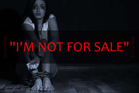 Concept of human trafficking. Text IM NOT FOR SALE and woman with chained legs and tied hands on background