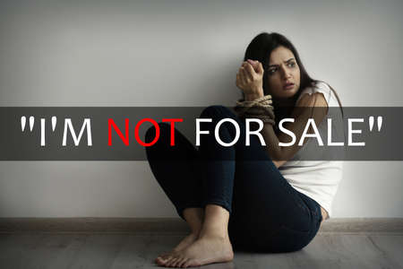 Concept of human trafficking. Text IM NOT FOR SALE and woman with tied hands on background
