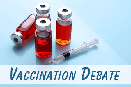 Vaccination debate concept. Vials and syringe with vaccine on blue background