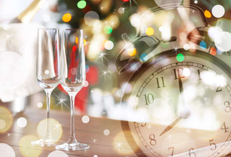 Countdown to holiday celebration. Alarm clock with champagne glasses and blurred Christmas tree on background