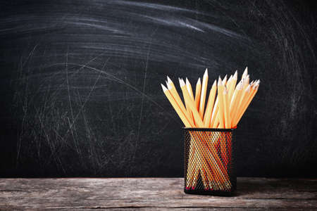 Holder with pencils on wooden table against school blackboard