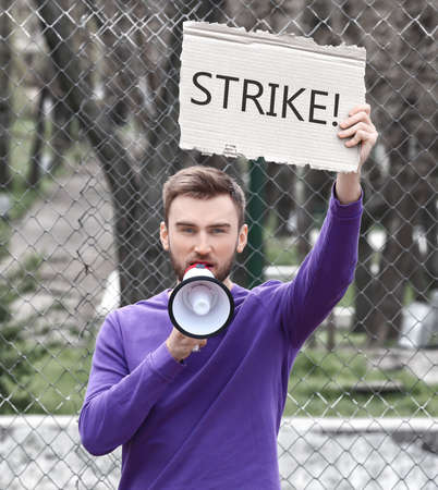 Young man with megaphone and placard on workers strike outdoor