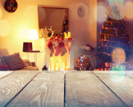 Wooden table and decorated room for Christmas celebration on background