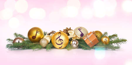 Composition with festive decorations and notes on color background. Concept of Christmas music and songs