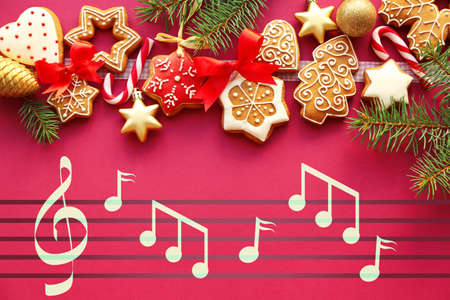 Tasty gingerbread cookies and notes on color background. Concept of Christmas music and songs