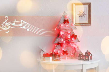 Handmade fir tree with garland on white table at home. Concept of Christmas music and songs