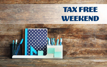 Office supplies and text TAX FREE WEEKEND on wooden background