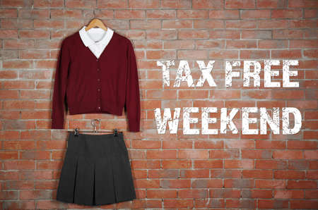 Text TAX FREE WEEKEND and school uniform on brick wall background