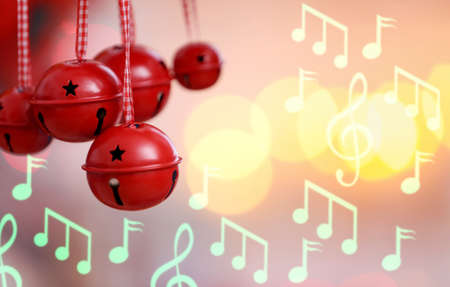 Jingle bells and notes on blurred lights background. Concept of Christmas music and songs Stock Photo