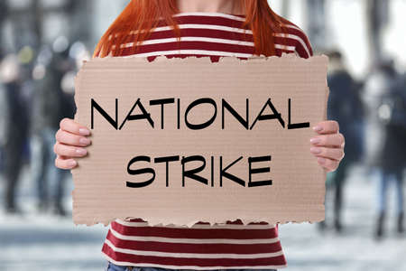 Young woman with placard and blurred crowd on background. National strike concept