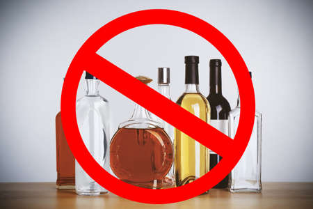 Different alcohol drinks in bottles with STOP sign on grey background