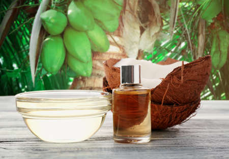 Glassware of coconut oil with nut on wooden table