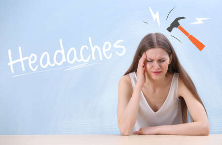 Young woman suffering from headache and drawn hammer on color background