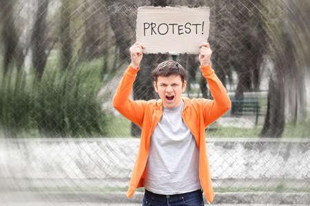 Hombre joven con cartel en huelga de trabajadores al aire libre Foto de archivo