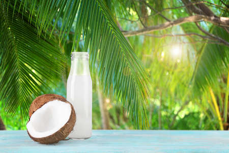 Glass bottle of coconut milk with nuts on wooden table