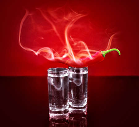 Smoking chili pepper and glasses with vodka on red background Stock Photo