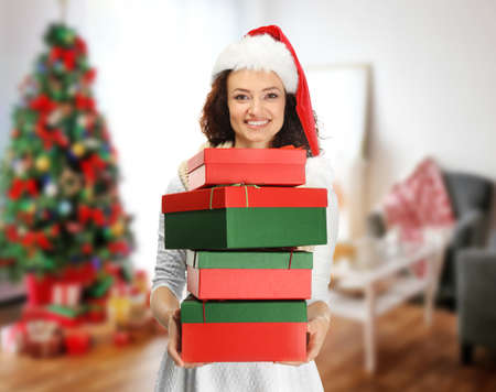 Young woman in Santa hat holding Christmas gifts and blurred interior on background