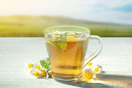 Thé à la camomille chaud dans la tasse avec des fleurs sur la table en bois en plein air Banque d'images - 92097209