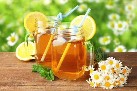 Hot chamomile tea in mason jars with flowers on wooden table outdoor
