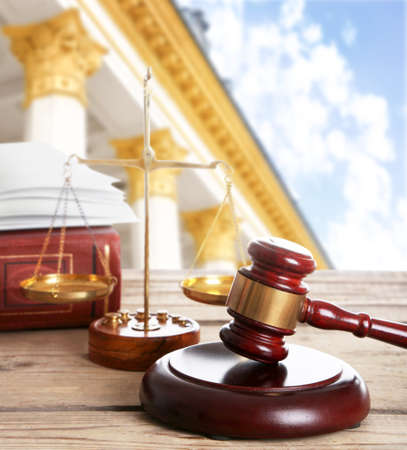 Judges gavel with scales and courthouse on background. Concept of law