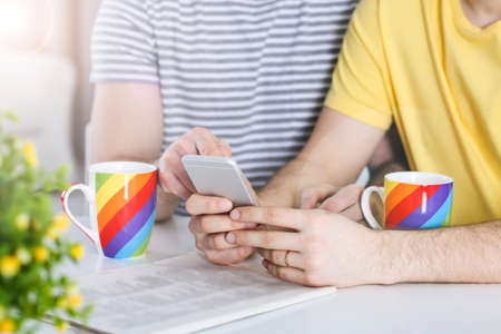 Gay couple using phone at table Stock Photo