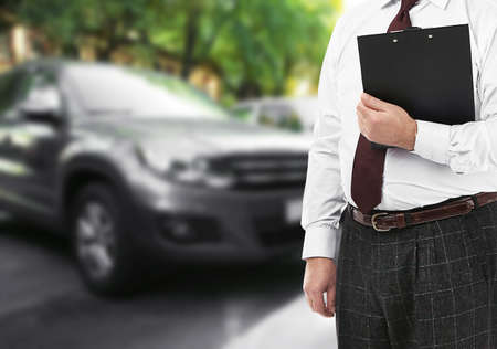 Insurance agent with clipboard and car on background Stock Photo