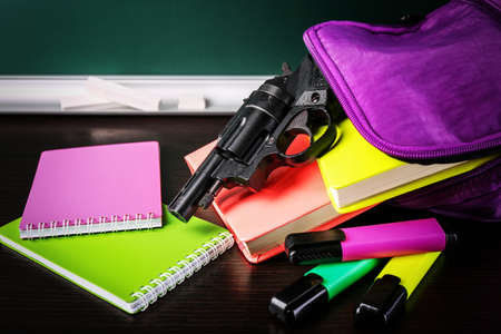 Backpack with gun and supplies on table. School shooting concept