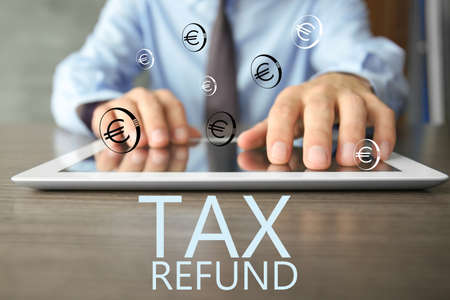 Man using tablet at table, closeup. Tax refund concept