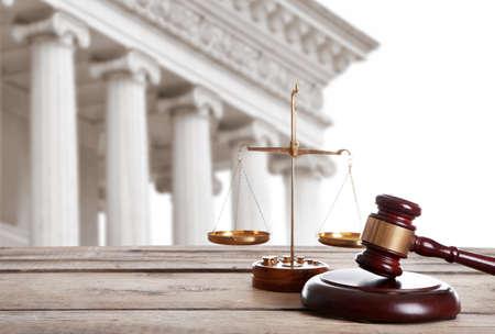 Młotek sędziowski z wagą i budynkiem sądu na tle. Pojęcie prawa
